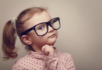 Thinking kid girl in glasses looking happy. Closeup instagram effect portrait